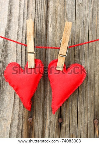 Two handmade red hearts of scrim on a red string