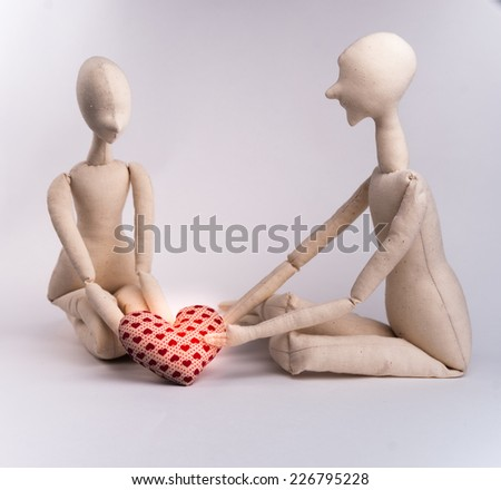 Two handmade textile dolls holding red heart. Image of love, affection.