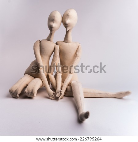 Two handmade textile dolls sitting together. Image of love, affection.