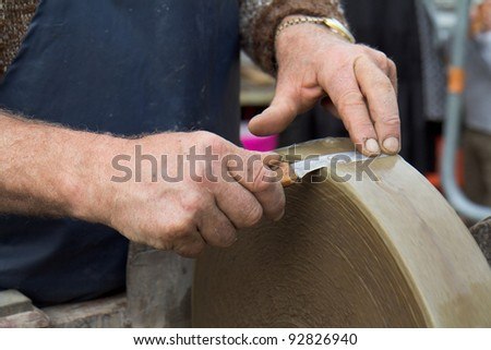 Two hands are holding a blade against a grindstone in motion.