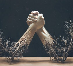 Two hands are holding together while twigs and braches are coming from the arms.