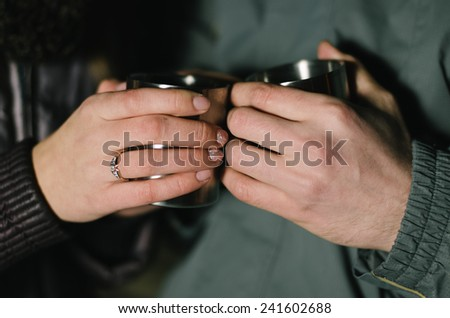 Two hands are holding two hot cups of tea