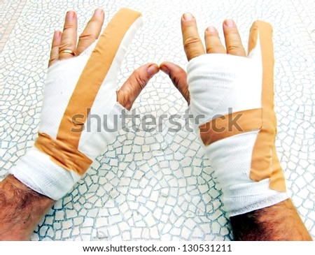 two hands breaking of bones wrapped in bandages