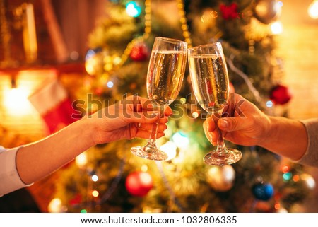 Two hands clink glasses with champagne, christmas #1032806335