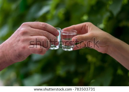Two hands clinking shots of alcoholic beverage together whishing best luck #783503731
