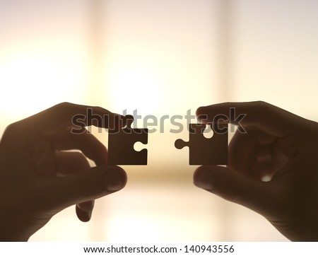 two hands collect puzzle, closeup