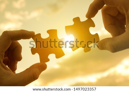 Two hands connect pieces of the puzzle against the sunset. Business concept idea, promotion, partnership, cooperation, teamwork, innovation.