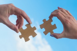 Two hands connect puzzle pieces against the sky. Business concept idea, cooperation, partnership, teamwork, innovation