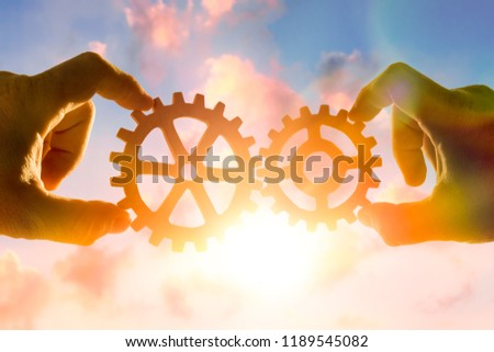 two hands connect the gears, the details of the puzzle. against the sky with sunset. Business concept idea, cooperation strategy, teamwork, innovation, creativity