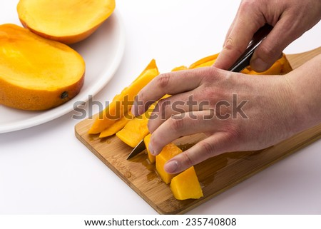 Two hands cutting mango chips into dice. The fingers of a left hand are fixing the fruit flesh on a wooden board, while the right is guiding a knife. Two mango slices on a plate. White background.