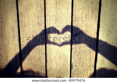two hands forming a heart shadow