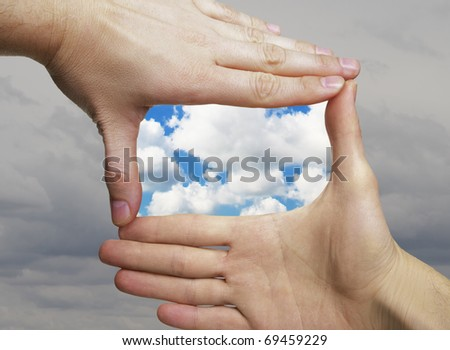 two hands framing fine weather cloudscape against gray sky