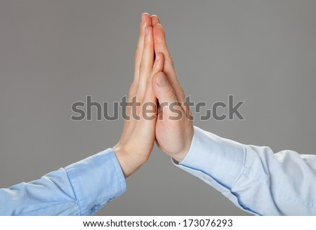Two hands giving high fives on grey background