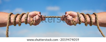 Two hands, helping hand, arm, friendship. Rope, cord. Hand holding a rope, climbing rope, strength and determination. Rescue, help, helping gesture or hands. Conflict tug of war