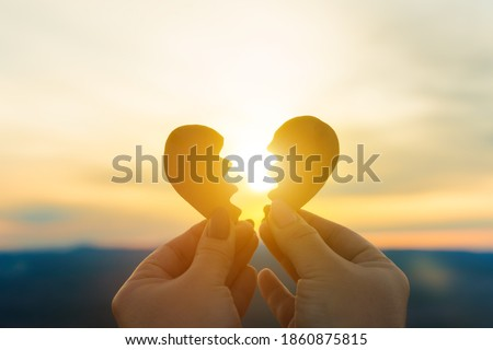 Two hands hold a broken heart on the background of the sunset. Concept spat divorce dissolution, love feelings Сток-фото ©
