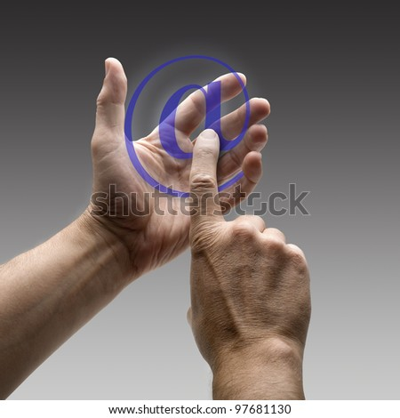 Two hands holding a at symbol. There is a route for hand and finger. - stock photo