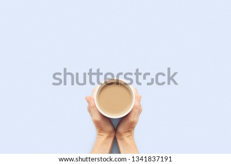 Two hands holding a cup with hot coffee on a blue background. Breakfast concept with coffee or tea. Good morning, night, insomnia. Flat lay, top view