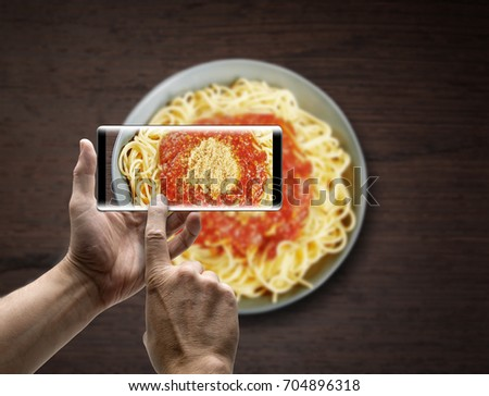 Two hands holding a mobile Smartphone and take a picture a Dish of spaghetti bolognese on wooden texture