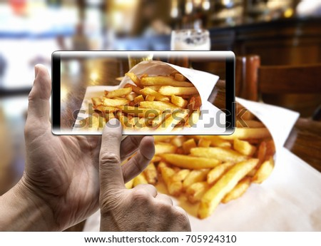 Two hands holding a mobile Smartphone and take a picture of Potatoes fries in a little white paper bag