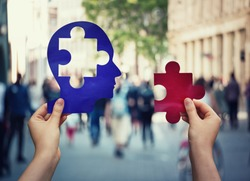 Two hands holding a paper with human head and a puzzle piece. Finding a cure to heal the disease. Mental health concept, memory loss and dementia disease. Alzheimer's losing brain and memory function.