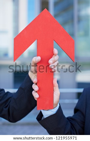 Two hands holding a red arrow pointing up