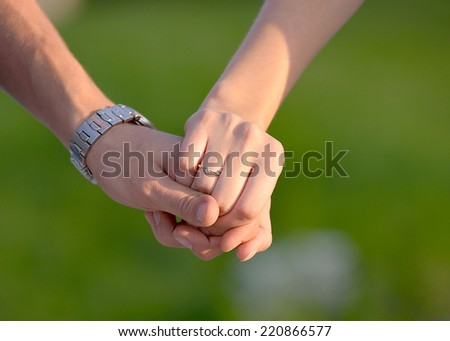 Two hands holding after engagement isolated on green background - stock photo