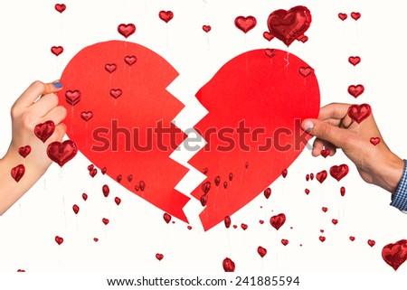 Two hands holding broken heart against red heart balloons floating