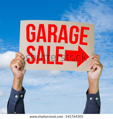 Two hands holding brown cardboard with garage sale on blue sky background