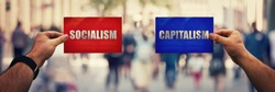 Two hands holding different colored paper sheet as socialist centralized economic planning versus capitalist liberated free market over crowded street background. Future strategy concept red vs blue.