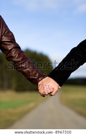 Two hands holding each other outdoor. Focus on hands, blurred way. Variation.