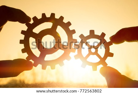 Two hands holding gears together. puzzle details on a sunset background. Close-up. Teamwork, partnership, business, cooperation and management concept. #772563802