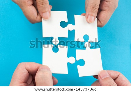 Two hands holding jigsaw puzzle pieces and putting them together
