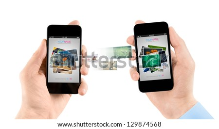 Two hands holding mobile smartphones while transferring pictures from one smart phone to another.