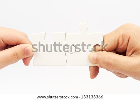 Two hands holding puzzle pieces and connecting them