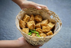 Two hands holding Tahu Sumedang in a bamboo basket looks from above. This food typical Favourite Sumedang food, West Java has a savory tofu flavour, view from top.