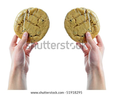 Two hands holding two cookies that are in shrink wrap isolated on a white background - stock photo