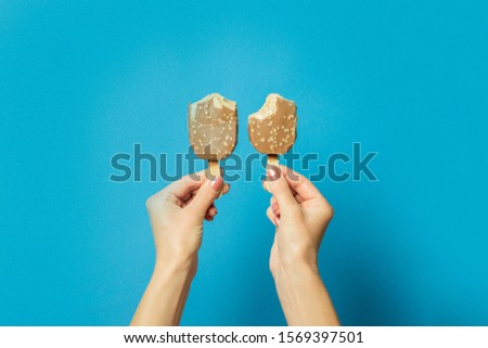 Two hands holds bitten ice cream on a stick on a blue background. Hot summer concept, a pair of lovers, lovers. Flat lay, top view #1569397501