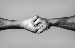 Two hands, isolated arm, helping hand of a friend. Rescue, helping hand. Male hand united in handshake. Man help hands, guardianship, protection. Black and white.
