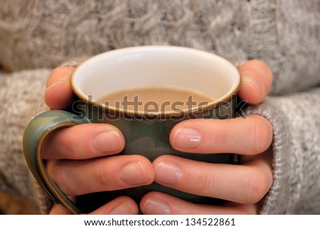 Two hands keeping warm, holding a hot cup of tea or coffee
