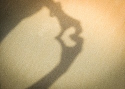 Two hands making love heart shadow symbol on the sand at the beach