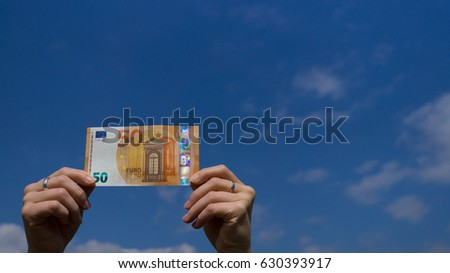 Two hands of a woman holding fifty euro banknote in the bottom left corner before blue sky outdoors - Shutterstock ID 630393917