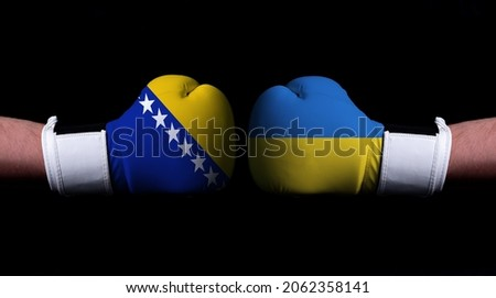 Two hands of wearing boxing gloves with Ukraine and Bosnia and Herzegovina flag. Boxing competition concept. Confrontation between two countries