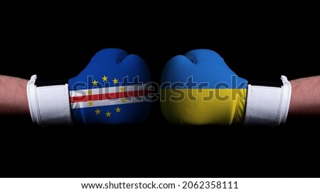 Two hands of wearing boxing gloves with Ukraine and Cape Verde flag. Boxing competition concept. Confrontation between two countries