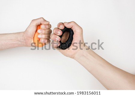 Two hands on a light background compete with each other - squeeze expanders to develop hand strength, the concept of competition, cooperation, power ストックフォト ©