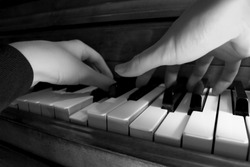 Two hands playing the piano - shallow focus