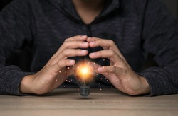 Two hands protecting the light bulb that is illuminating on the table. Creative protecting patents and ideas concept.
