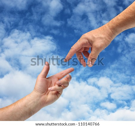 Two hands reaching towards each other blue sky background