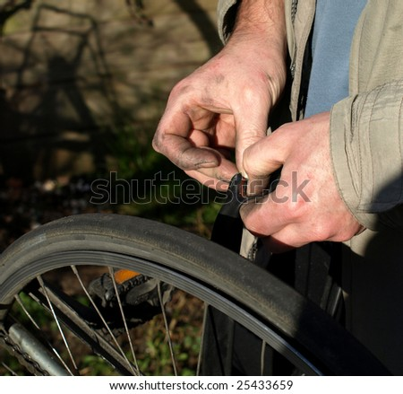 Two hands repairing a flat tire