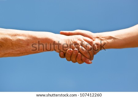 two hands shaking hands over blue sky