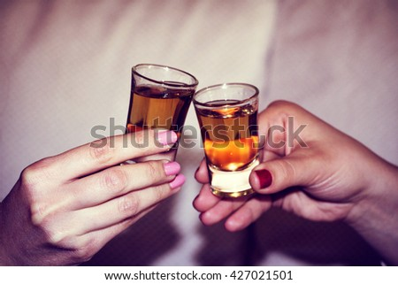 Two hands toasting whiskey on white background